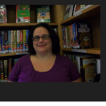 Kristin Jaques smiling in front of a library bookshelf.