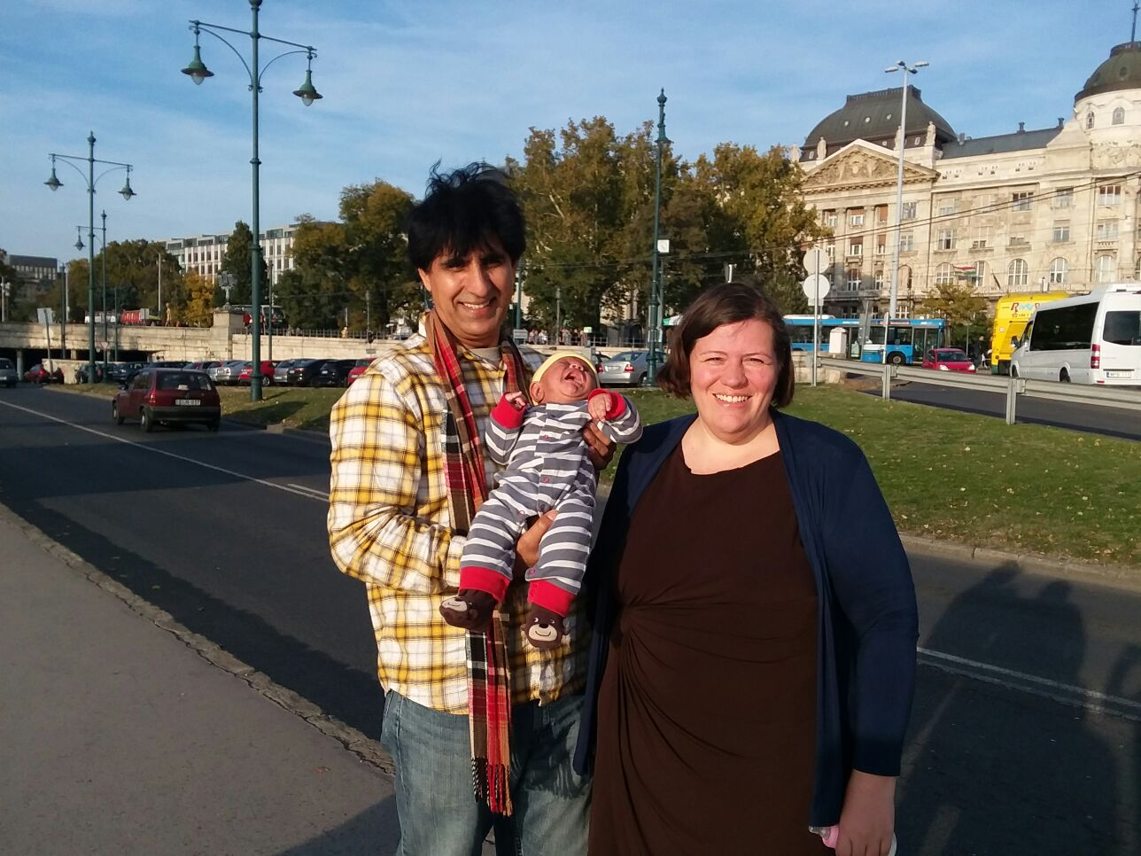 Naomi, Sana and their baby standing in front of a building in the sun in Budapest, the baby is crying and we are smiling.