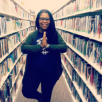 Amanda M. Leftwich is standing between two rows of bookshelves in a library. She is doing a yoga pose that inspires mindfulness.
