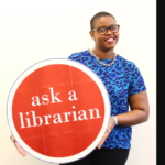 Aisha Conner-Gaten is standing wearing a blue shirt and against a white background. She is holding a round red sign that says the words Ask a Librarian, the text is white.