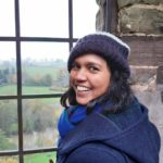 Natasha S. Chowdory photo for INALJ interview, is taken outdoors and she wears a blue coat and looks over her shoulder