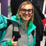 Samantha Sergeant Interview photo for INALJ wearing a blue and grey jacket, backpack and glasses