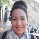 Grecia Álvarez headshot for INALJ Interview with hair up and grey scarf